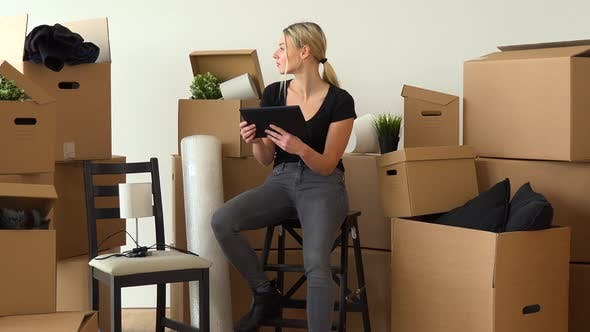 Thumbnail for A Moving Woman Sits on a Chair in an Empty Apartment and Works on a Tablet, Surrounded By Boxes
