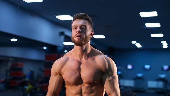 Athletic man in gym is posing to the camera. Bodybuilder with perfect body.