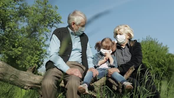 Thumbnail for Grandparents with Granddaughter in Medical Masks in Park. Coronavirus Quarantine