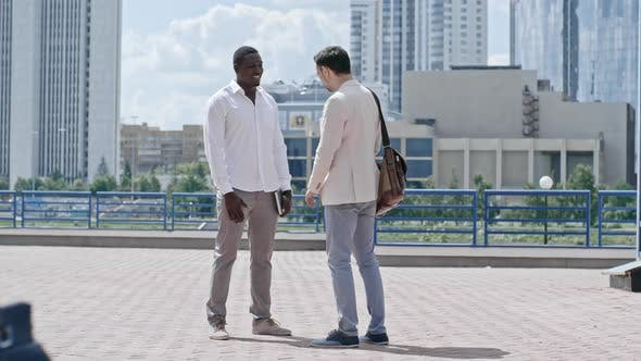 Thumbnail for Business Partners Shaking Hands while Talking Outdoors