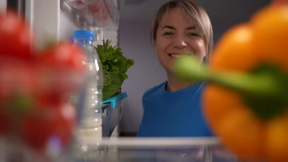 Positive erwachsene Frau nimmt Gemüse aus dem Kühlschrank
