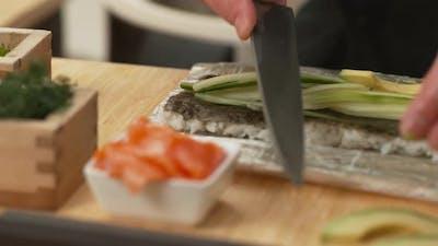 Sushi chef preparing sushi rolls