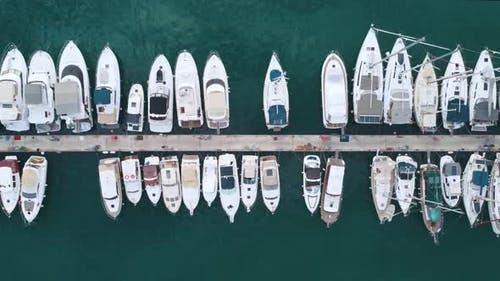 Fly over yachts moored at the pier.