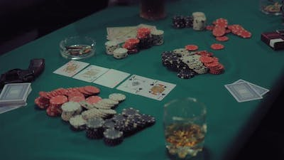 Combination of Cards Stacks of Chips Money and Alcohol on the Playing Table