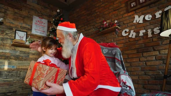 Thumbnail for Little Girl Comes To Santa Claus, Presents New Year Gift and Hugs Christmas Grandfather