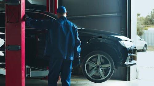 Autoservicearbeiter Heben Fahrzeug auf Hebezeug vor der Wartung in der Werkstatt
