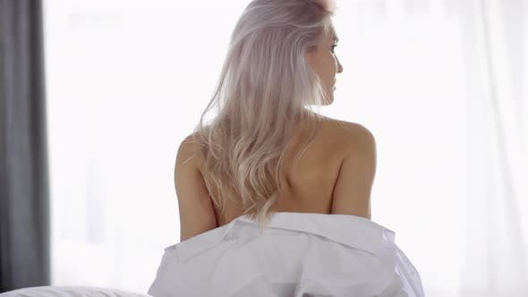 Thumbnail for Bare Back of Young Woman Taking off White Shirt by Window