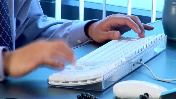 Thumbnail for Young Asian businessman typing on computer at desk