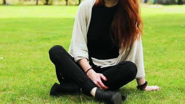 Thumbnail for Redhead woman sitting on grass