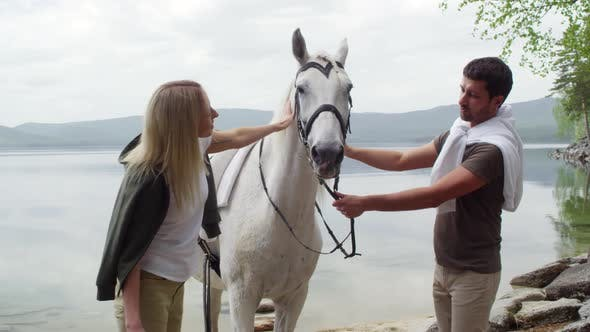 Thumbnail for Couple Petting Beautiful White Horse