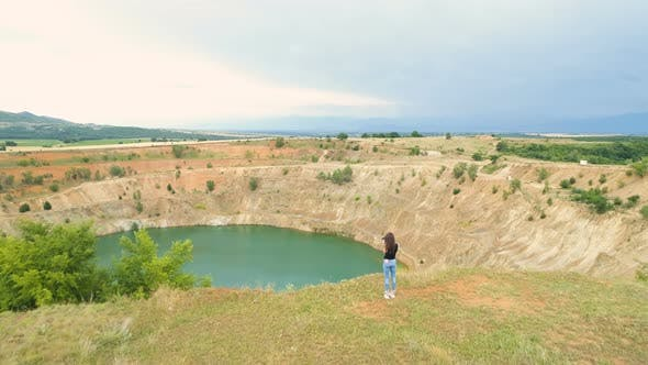Lone Active Woman at the Edge of Abandoned Copper Mine Pit Taking Photos with Camera