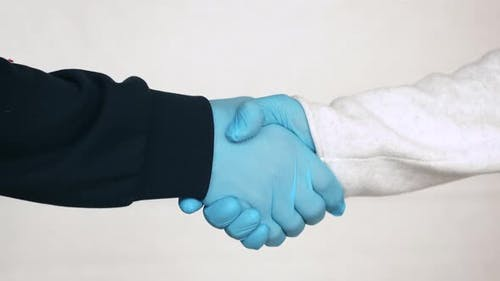 Handschlag in medizinischen Handschuhen