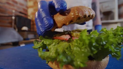 The Cook Hands Placing Top Bun on a Burger. Close Up. Slow Motion