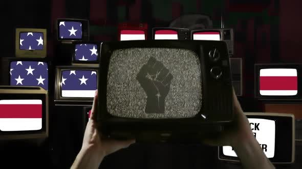 Hands rising Old TV Set with Clenched Fist on its Screen over American Flag.