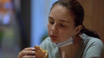 Woman at Hard Work Taking a Break to Eat Burger