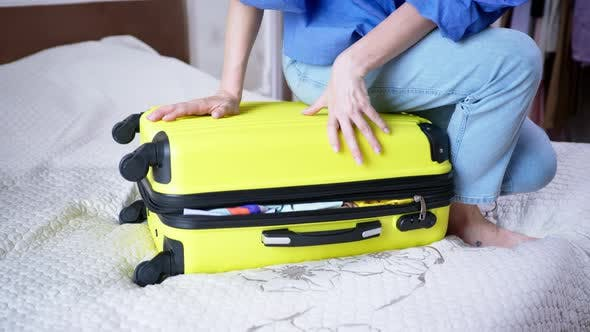 Thumbnail for Travel Suitcase, Young Woman Tries To Close Her Case with Things Sits on Top and Closes the Zipper