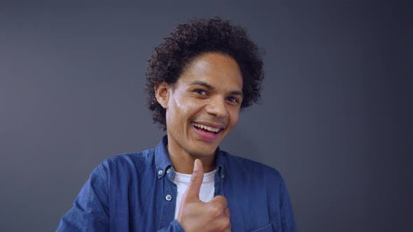 Thumbnail for Curly Afro-american Guy Showing Thumb Up on Studio Background.