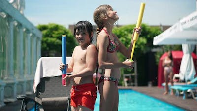 Side View of Confident Caucasian Children Standing at Swimming Pool with Water Gun Back to Back and