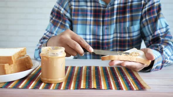 Young Man Eating Peanut Butter and Bead While Sited