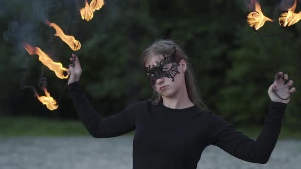 Cover Image for Portrait of Young Beautiful Woman in Mask Performing a Show with Flame in Front of Trees. Skillful