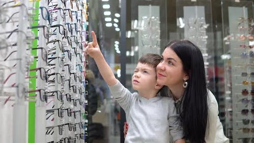 Young Woman with Baby Mother and Son Choosing Glasses in Optics Store