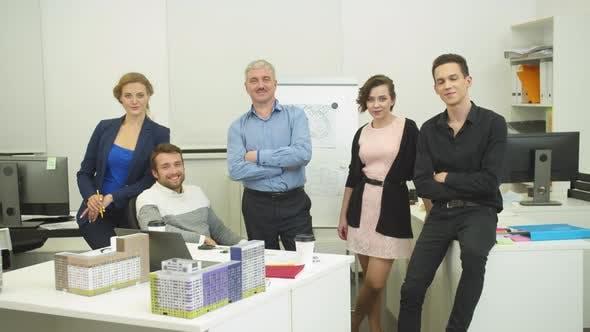 Thumbnail for Arbeitskameraden stehen zusammen im Büro über das Modell der Häuser und Lächeln