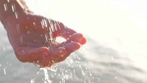 Thumbnail for Weibliche Schellen Hand fängt fallende Wassertropfen auf Meereslandschaft Hintergrund