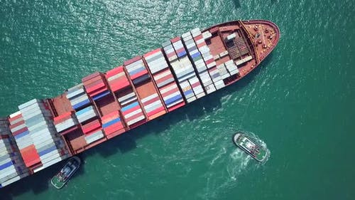 Top view of cargo ship crossing the harbor