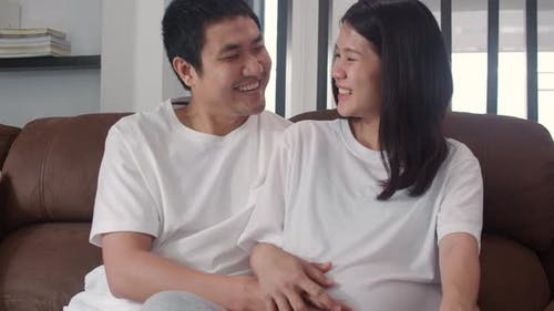 Young Asian Pregnant man touch his wife belly talking with his child feeling happy smile peaceful