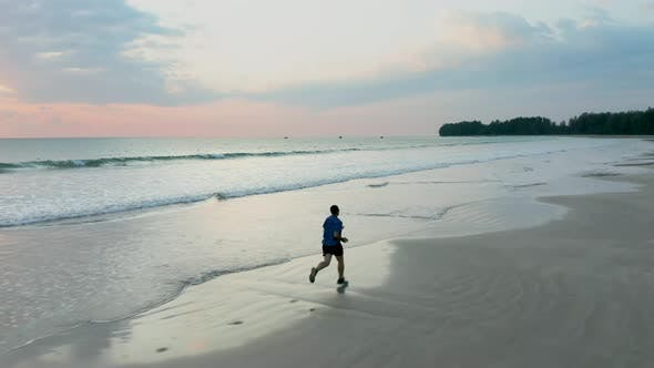 Thumbnail for Jogger on a tropical beach at sunset
