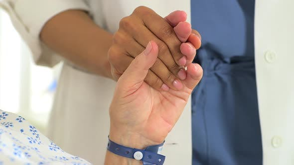 Thumbnail for Close-up of Female African doctor holding her Caucasian patient's hand