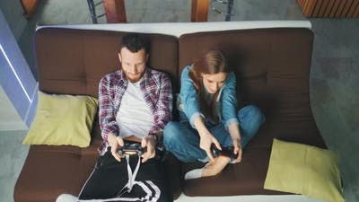 A Couple of Young Adults is Playing Video Games at Home