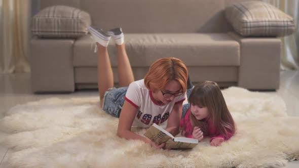 Thumbnail for Mom Reads the Girl a Book. Portrait Beautiful Mother and Cute Little Daughter Are Lying on the
