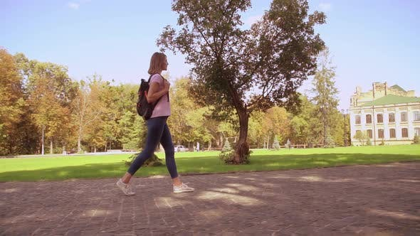Cover Image for Happy Woman with Rucksack Walks in Campus Area