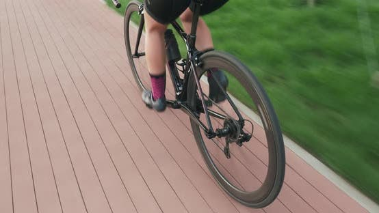 Thumbnail for Woman is cycling in park. Athletic female in sportswear rides on bike on cycle path, tracking shot.
