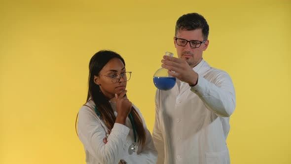 Thumbnail for Multiethnic Man and Woman in Lab Coats Looking on Flask with Experimental Liquid on Yellow