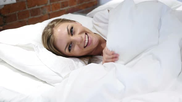 Thumbnail for Happy Woman peeking out from her blanket in bed and Smiling
