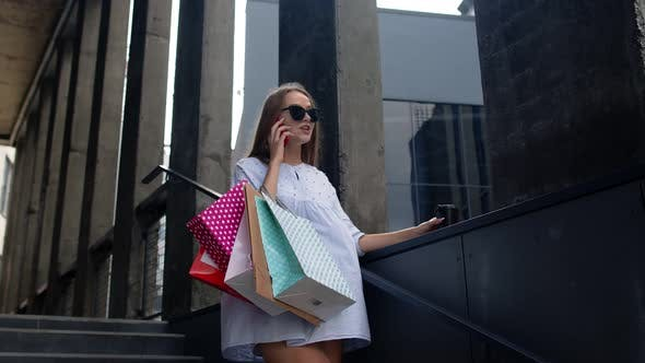 Thumbnail for Girl Staying Near Shopping Mall with Shopping Bags and Talking on Mobile Phone About Purchases
