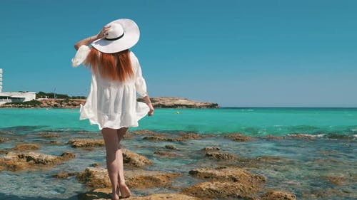 Woman Tourist White Dress Standing on Beach with Crystal Clear Water