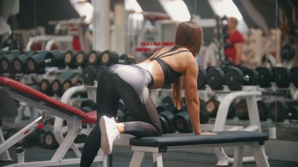Eine Sportlerin Frau Training in der Turnhalle - Training Ihre Arme - Ziehen Sie die Hantel im Stehen auf