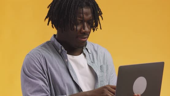 Thumbnail for Studio Shot of Young African American Guy with Dreadlocks Browsing on Laptop  Orange Background