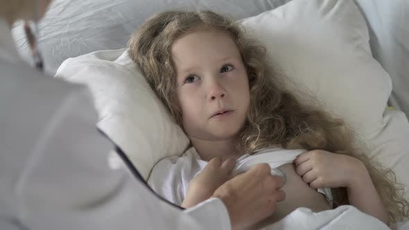 Thumbnail for Sick Kid Lying in Bed and Crying While Doctor Examining Her