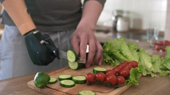Thumbnail for Handicapped Man with Bionic Prosthesis Cutting up Vegetables