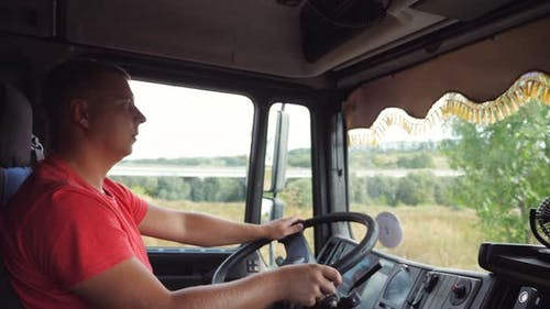 Lorry Driver Operating the Truck Through Countryside at Sunny Day