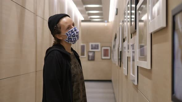 Young Woman Wearing Face Mask Looking at Pictures in Photography Gallery