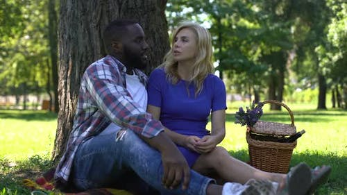 Girlfriend and Boyfriend Discussing Relationship on Picnic, Biracial Love, Relax