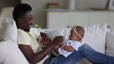 Affectionate Dad Playing with Infant Daughter