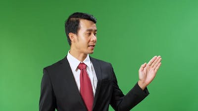 Asian Businessman Pointing On Something And Talking On A Green Screen, Chroma Key