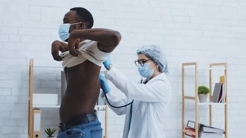 Doctor Examining Black Male Patient with Stethoscope for Diagnostic Sars or Coronavirus