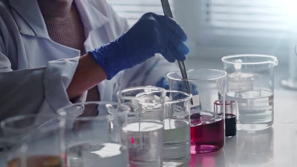 Laboratory Worker Scientist Laboratory Assistant Tests Chemicals for Reactions in Flask Interfering